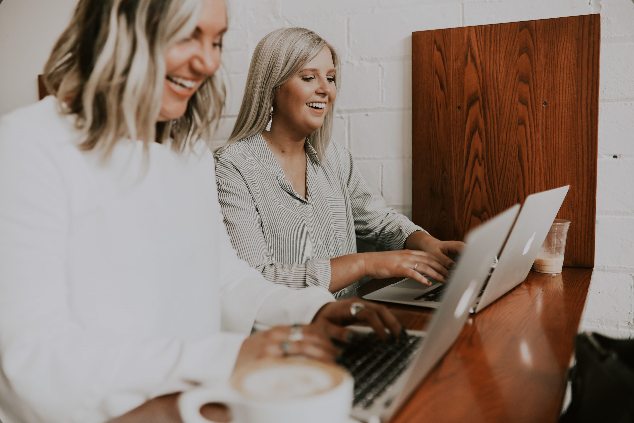 two women typing on computer